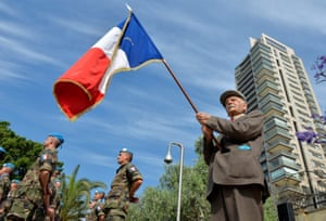 A second world war veteran, 91-year-old Kamal Abed al-Nour, who fought with French troops, carries a French flag during a ceremony in Beirut, Lebanon