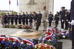 France's president François Hollande rekindles the eternal flame at the tomb of the Unknown Warrior at the Arc de Triomphe in Paris