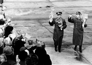 Leonov, left, and Belyayev wave to crowds after arriving at Moscow airport, on 23 March, 1965, travelling from the Baikonur cosmodrome to be feted as heroes at a Red square rally.
