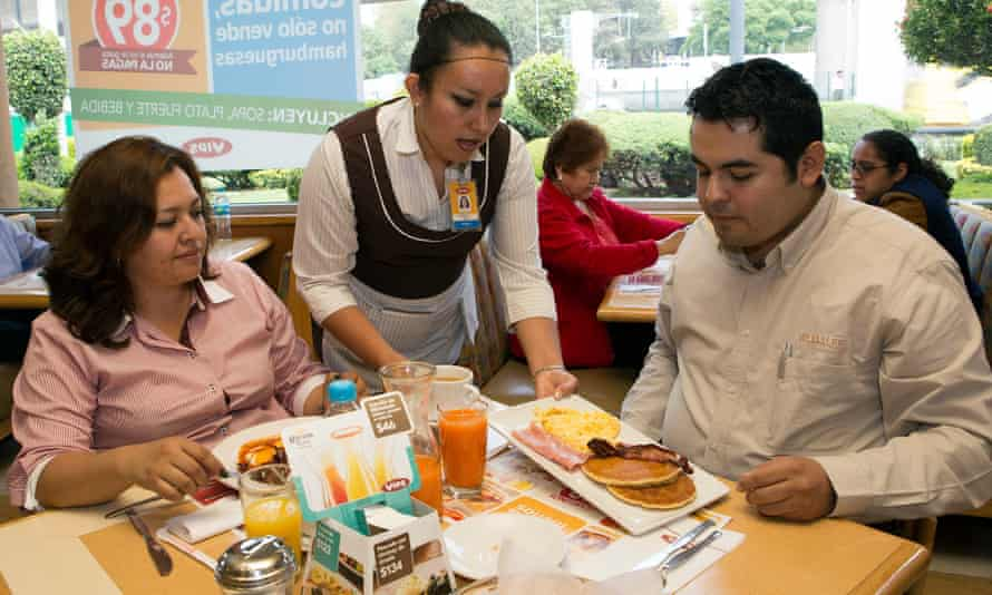 A waitress serves breakfast to customers