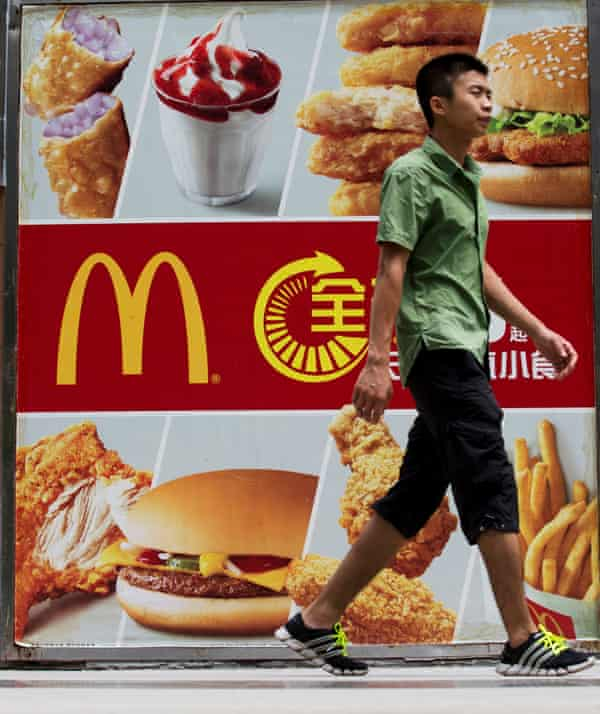 A pedestrian walks past an advertisement for McDonald's Corp. in the Futian district of Shenzhen, China.