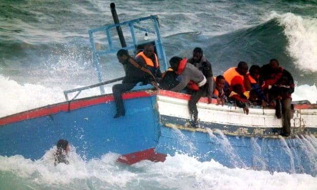 Rescuers help stranded coming from Libya from a boat that crashed into rocks as they tried to enter the port of Pantelleria, an island off the southern coast of Italy.