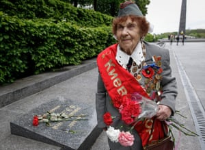 Ivanchenko Emilia, a second world war veteran, carries flowers near the tomb of the Unknown Warrior in Kiev, Ukraine