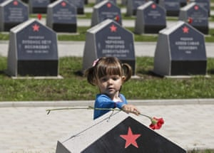 A Russian girl touches a carnation left on a grave stone of  a Soviet serviceman killed in Romania, at the Soviet Heroes cemetery in Bucharest