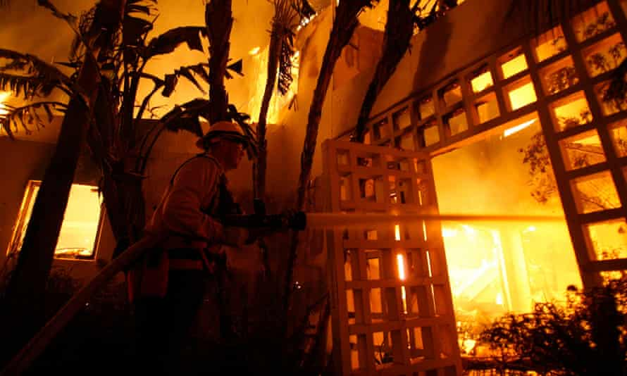 A fireman sprays water on a house burning during the Jesusita wildfire in Santa Barbara, California.