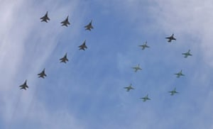 Mikoyan-Gurevich MiG-29 Fulcrum fighters and Sukhoi Su-25SM Frogfoot ground-attack planes form a number 70 as they fly over Red Square