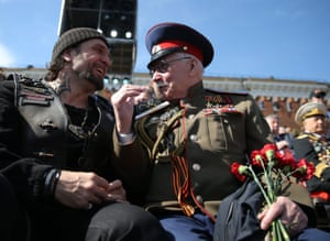Night Wolves motorcycle club leader, Alexander Zaldostanov AKA 'Surgeon', speaks with a veteran during the parade