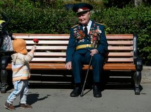 A girl gives a flower to a blind second world war veteran