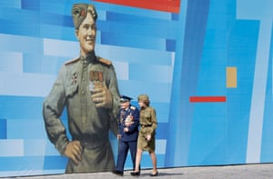 A second world war veteran accompanied by a woman dressed in a Red Army soldier-style uniform arrives at Red Square