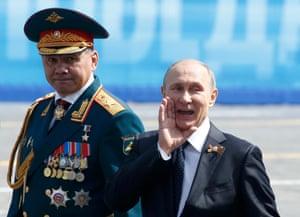 Russia's president, Vladimir Putin, greets veterans next to the defence minister, Sergei Shoigu