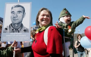 A woman with a child holds a picture of a second world war soldier as she takes part in the Immortal Regiment march in Divnogorsk, Russia
