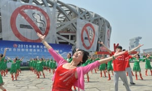 Dancers perform in front of anti-smoking banners displayed on the Beijing National Stadium on World No Tobacco Day on 30 May