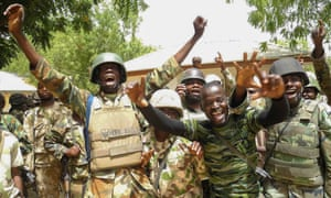 Nigerian soldiers celebrate after recapturing areas of Baga, north east Nigeria earlier this year.