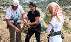 Will Harris of Wadi Climbing helps Summer Rushdi with her belaying technique on a climbing course at Ein Qiniya in the occupied Palestinian territories watched by 16 year Rubaa Bledi who will do her first rock climb a few minutes later.