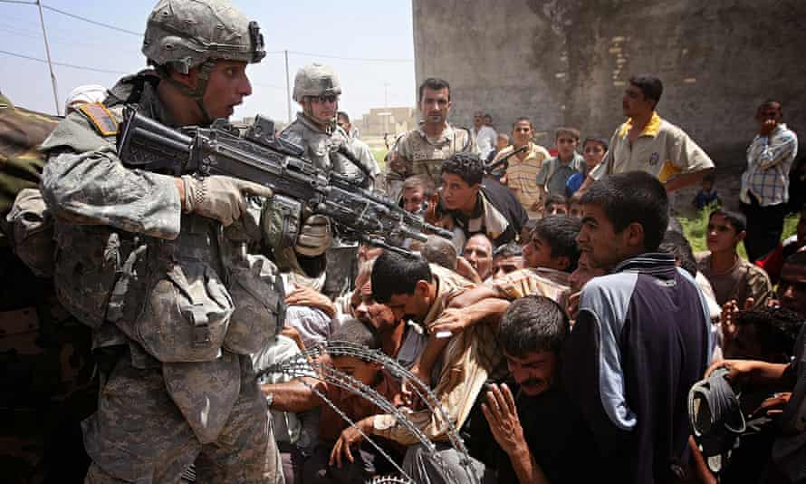 a US soldier gestures with his gun as Iraqis rush to receive humanitarian aid in Baquba, north of Ba