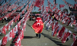 A man walks with a flag of the Nationalist Movement party (MHP) during a campaign rally in Istanbul.