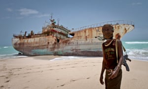 A Somali pirate in front of a hijacked fishing boat in 2012.