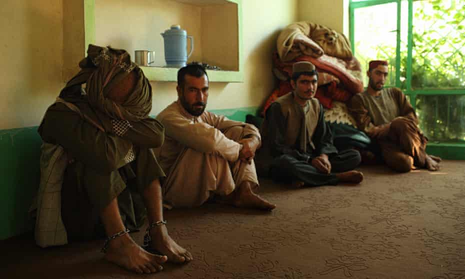 A patient in ankle shackles waits for treatment with others at the drug rehabilitation centre in Tarin Kot.