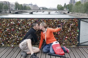 A couple kisses and takes a selfie in front of the padlocks