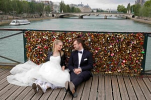 """A recently-married couple from Poland, Dominika and Bartek Mieczkowski, sit near an iron grill coered with """"love locks"""" on the Pont de Arts in Paris, France."""