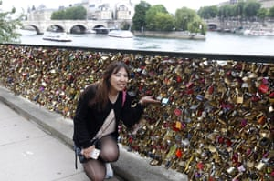 A tourist poses in front of the love Padlocks on the Pont des Arts