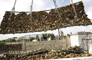 City municipal employees remove the barriers with love padlocks on the Pont des Arts