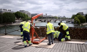 """Workers remove panels bearing """"love padlocks"""" attached on the railings of the Pont des Arts bridge"""