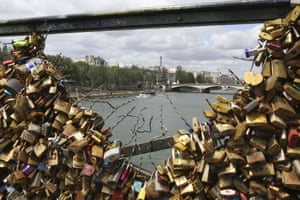 The Eiffel tower appears through the partly lock-free railing of the famed Pont des Arts bridge in Paris