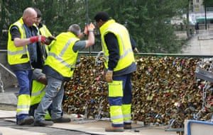 Paris city employees remove a railing loaded with locks on the famed Pont des Arts bridge in Paris