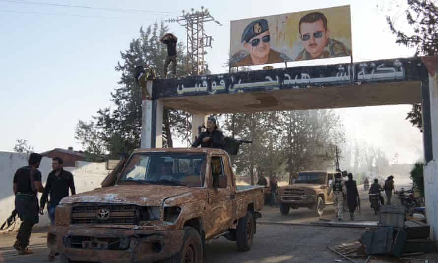 Posters of Syrian president Bashar Al-Assad and his father Hafez Al-Assad are seen at the main entrance at the Brigade 52 military base after it was captured by the Free Syrian Army in Daraa.
