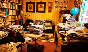 A private study with piles of papers covering every surface and on the floor.