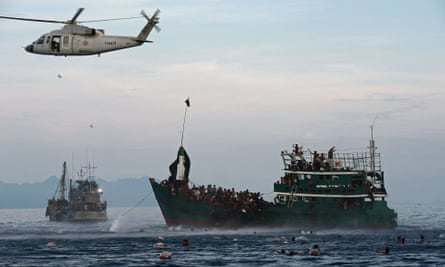 Rohingya migrants swim to collect food supplies dropped by a Thai army helicopter. Rohingya migrants fled Burma in droves this spring in the face of persecution in their country.