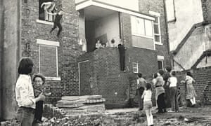 Boys jump from a second storey window of a derelict house while other children watch