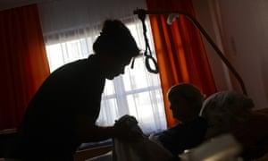 nurse helping an older woman in a nursing home