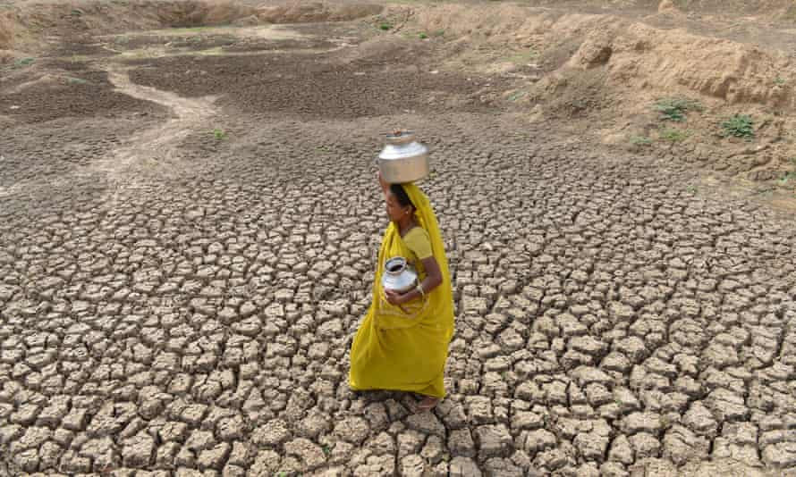 An Indian woman carries an empty water pot as she crosses the dry bed of a pond at Mehmadpur village.