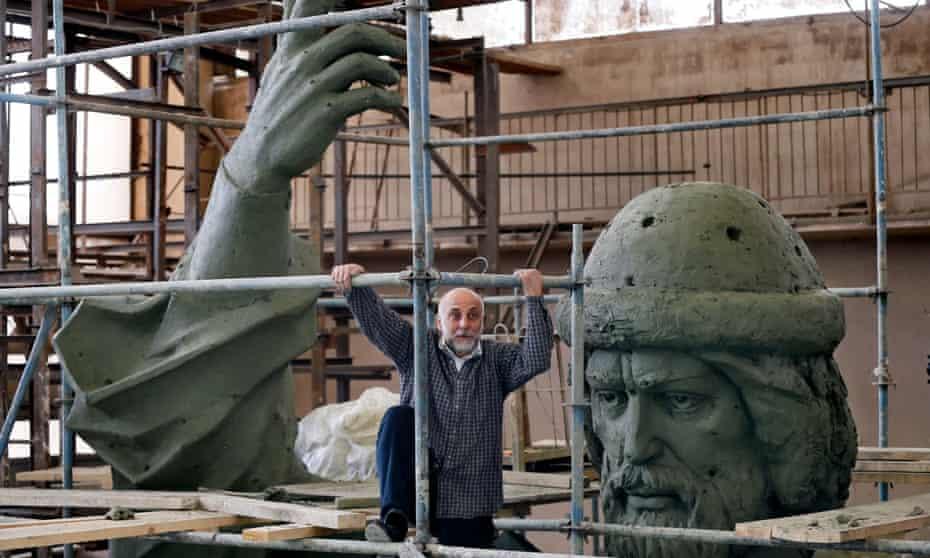 Russian artist Salavat Scherbakov poses beside his huge sculptor of Vladimir the Great in his Moscow workshop.