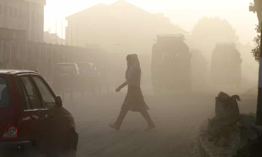 A Kashmiri woman covers her face as she crosses a dusty road in Srinagar, India. The WHO puts 13 Indian cities in the world's 20 most polluted, with Delhi deemed the filthiest.