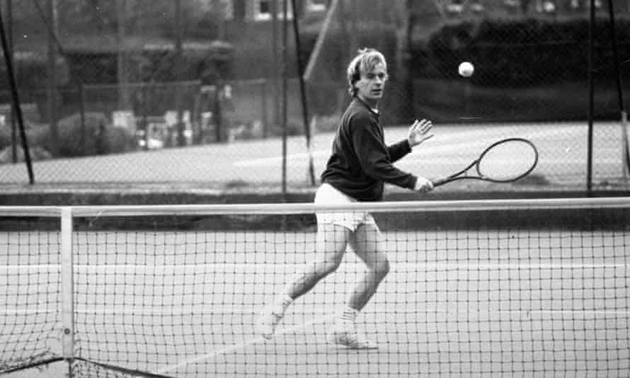 Author Martin Amis making a backhand return as he plays tennis.