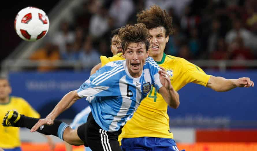 Argentina's Gabriel Heinze heads the ball away from Brazil's David Luiz during the friendly in Doha.