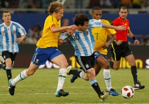 Lionel Messi takes the ball away from Brazil's Lucas Leiva in Doha, Qatar.