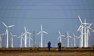 Workers walk near wind turbines for generating electricity, at a wind farm in Guazhou, 950km (590 miles) northwest of Lanzhou in China.