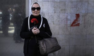 A woman in Cairo holds holds a red flower in protest at the death of the Egyptian poet Shaimaa al-Sabbagh, who was killed when police fired at unarmed demonstrators in January.