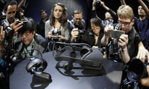 Photographers take pictures of the new Oculus Rift virtual reality headset and touch input device following a news conference Thursday, June 11, 2015, in San Francisco.