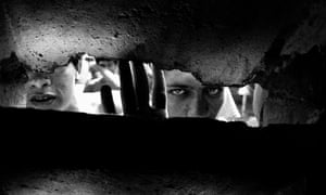 Prisoners stare through a hole in a wall at Los Teques jail, Caracas, Venezuela.