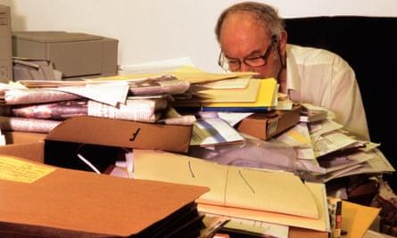 Man reads desk full of legal documents.