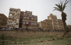 People gather to look at houses destroyed by Saudi air strikes in the old city of Sana'a, Yemen