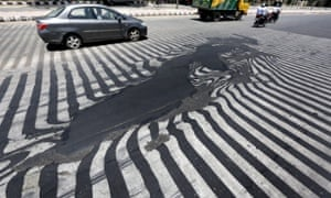 Road markings appear distorted as the asphalt starts to melt due to the high temperature in New Delhi, India, 27 May 2015.