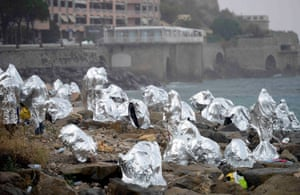 Menton, France A group of migrants keep themselves warm with emergency blankets on the seawall on the border with Italy. 200 mainly African migrants attempted to cross the border on Saturday but were blocked by Italian police and French gendarmes.
