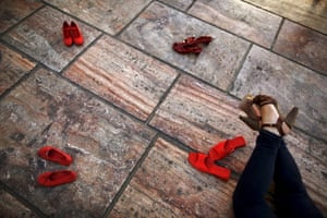 Malaga, Spain A woman lies on the floor next to an art installation of 745 pairs of red shoes, part of an installation by the Mexican artist Elina Chauvet which protests against domestic violence.
