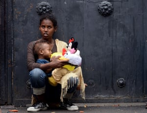 A mother holds her child with toys brought by aid workers outside Baobab migration centre next to the Tiburtina train station in Rome.